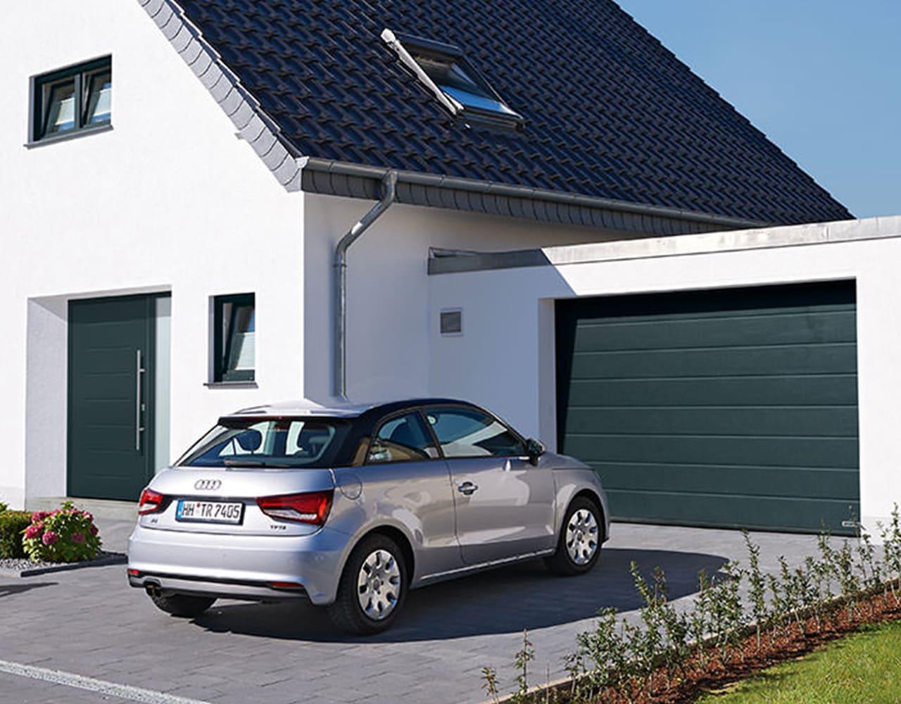 Garagentore und Haustüren eingebaut in einem Einfamilienhaus mit Auto vor der Garage.